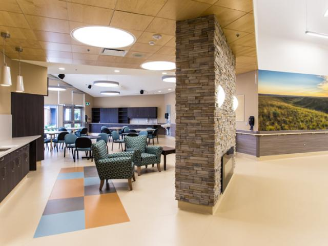 Kerrobert Integrated Healthcentre. Interior showing fireplace, dining area and wall with large mural.