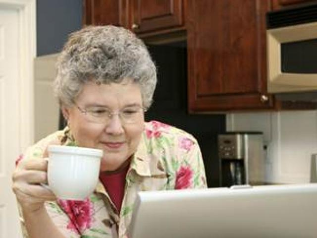 A senior woman sits in her kitchen holding a coffee cup in her right hand as she reads on her laptop computer.