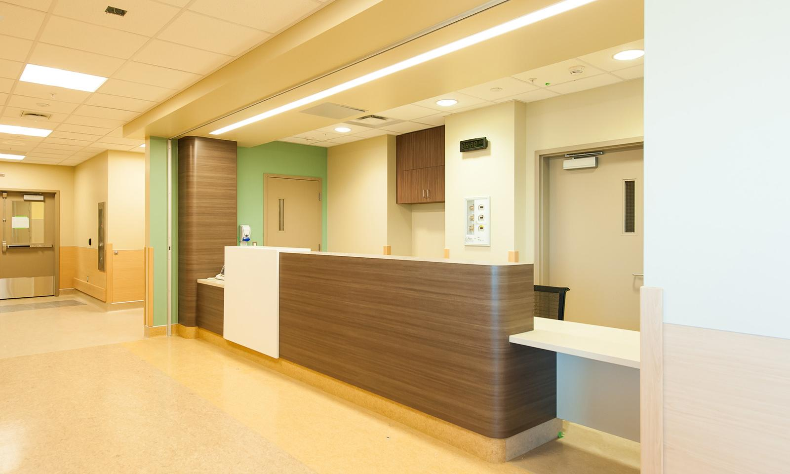 Calgary South Health. Reception desk with brown wood laminate and rounded corners. Pale green accent wall.