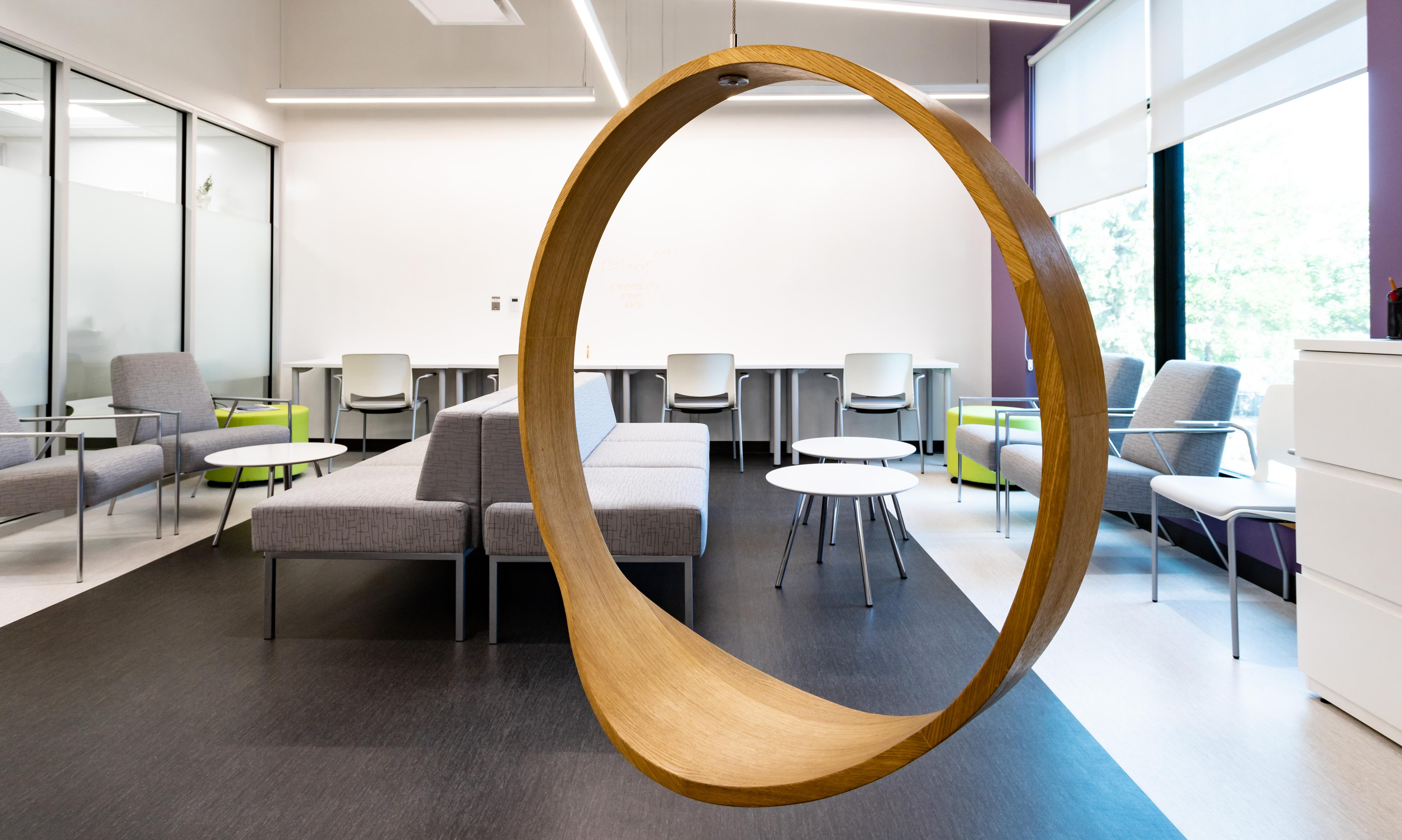 Seven Oaks General Hospital, Chronic Disease Innovation Centre. Modern office lounge with a round swing in the foreground.
