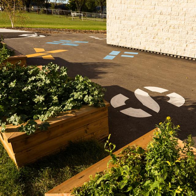 Lord Nelson School. Just outside the gym there are several wooden planters filled with lush plants. Colourful stencils of giant numbers and letters can be seen on the pavement.